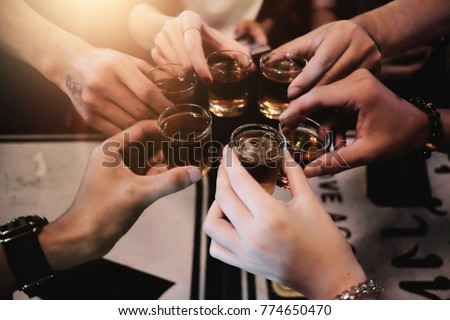 Cheers clinking of friends with bourbon whisky drink in party night after work on colorful background #774650470