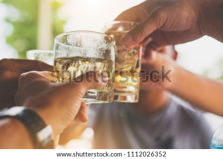 Cheers clinking of friends with  whisky drink in party evening after work