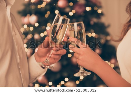 Cheers!Close up photo of two people holding glasses of shampagne on xmas. #525805312