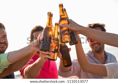 Cheers! Group of happy young people are toasting with bottles of beer in the beach. Celebration concept  #1110513077