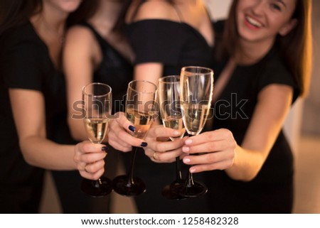 Cheers! Group of people cheering with champagne flutes with holiday lights on background with copy space. #1258482328