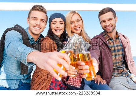 Cheers! Group of young happy people cheering with beer and smiling while bonding to each other