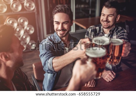 Shutterstock Cheers, my friends! Three handsome men are drinking beer, celebrating meeting and smiling.