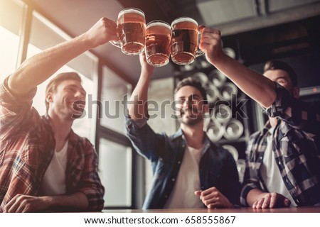 Cheers, my friends! Three handsome men are drinking beer, celebrating meeting and smiling.