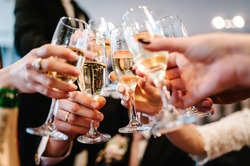 Cheers! People celebrate and raise glasses of wine for toast. Group of man and woman cheering with champagne.