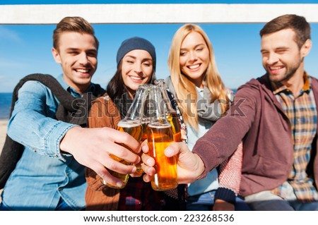 Cheers to friends! Group of young cheerful people cheering with beer and smiling while bonding to each other