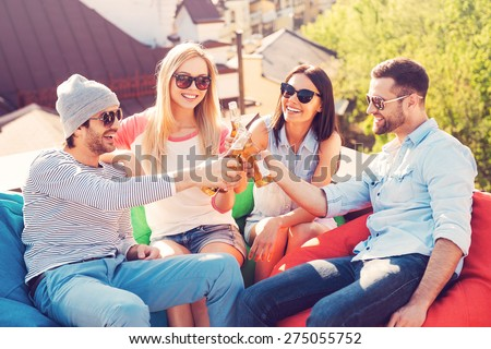 Cheers to friends! Top view of four young cheerful people cheering with beer and smiling while sitting at the bean bags on the roof of the building