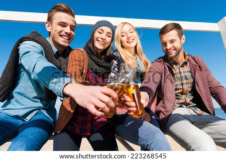 Cheers to friendship! Low angle view of four young cheerful people cheering with beer and smiling while bonding to each other