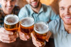 Cheers to success! Top view of three happy young men in casual wear toasting with beer while sitting in bar together