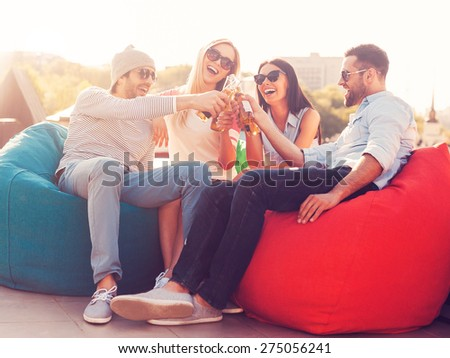 Cheers to us! Four young cheerful people cheering with beer and smiling while sitting at the bean bags on the roof of the building