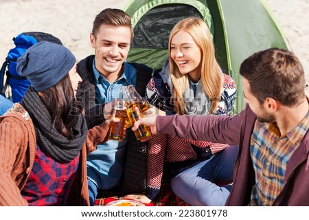 Cheers to us! Top view of four young happy people cheering with beer and smiling while sitting near the tent together