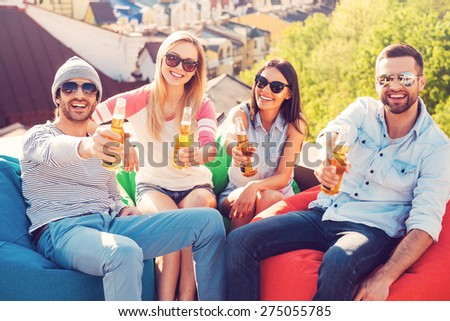 Cheers! Top view of four young cheerful people holding bottles with beer and cheering with you while sitting at the bean bags on the roof of the building