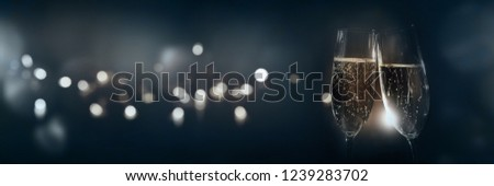 Cheers with tingling champagne on dark blue background and golden bokeh for a celebration #1239283702