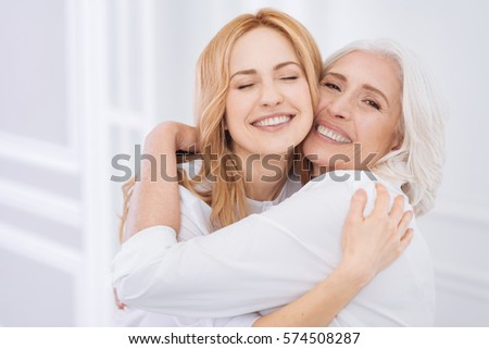 Cheerul senior woman and her daughter embraing