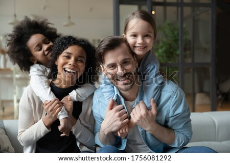 Cheery African and Caucasian girls cuddle piggy back multi-racial parents loving mom and dad seated on sofa in living room. Happy multinational family portrait, new home funny weekend together concept