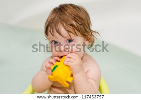Cheery cute baby girl plays with rubber toys and smiles in a full of water bath. Portrait.