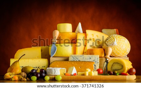 Cheese and food on wooden table. Different types of cheese
