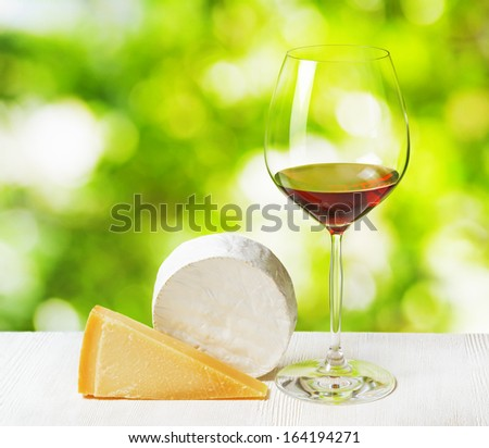 Cheese and glass of wine on nature background.