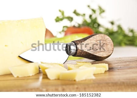 Cheese and knife on a wooden board