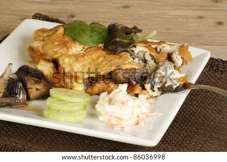 cheese and mushroom omelette with coleslaw mushrooms and cucumber on a wooden table