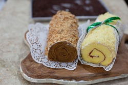 Cheese and nougat roll cake wrapped in doily paper and tied with a green bow, ready to pack, selective focus