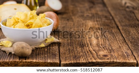 Cheese and Onion Potato Chips on an old wooden table as detailed close-up shot (selective focus)