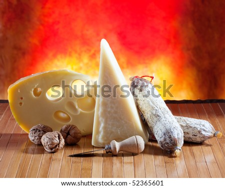 Cheese and salami on a wooden surface with colored background #52365601