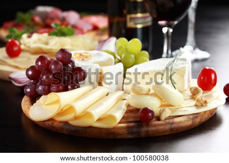 Cheese and salami platter with vegetable and herbs
