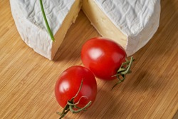 Cheese and tomatoes on wooden desk. Close-up shoot.