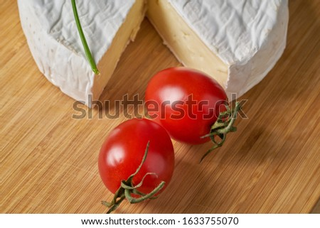 Cheese and tomatoes on wooden desk. Close-up shoot. Stockfoto ©
