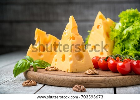 Cheese and vegetables on a wooden table, piece of cheese