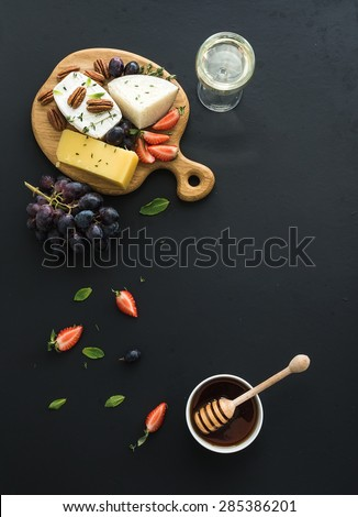 Cheese appetizer selection or whine snack set. Variety of cheese, grapes, pecan nuts, strawberry and honey on round wooden board over black backdrop, top view, copy space