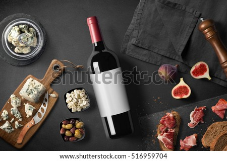 Cheese appetizer selection or wine snack set. Red wine, variety of cheese, figs, bread, olives and prosciutto on wooden board over black backdrop, top view, copy space