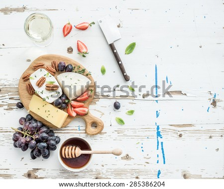 Cheese appetizer selection or wine snack set. Variety of cheese, grapes, pecan nuts, strawberry and honey on round wooden board over rustic white backdrop, top view, copy space