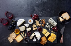 Cheese assortment on slate cutting board with wine. Grey background. Top view. Copy space.