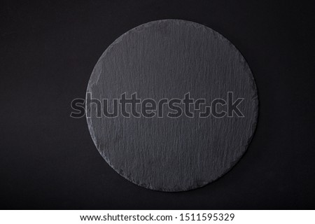 Cheese basalt round  stone board, cheese stand, slate platter.   Cheese basalt round  stone  slate, close up.