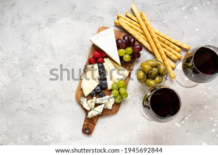 Cheese Board Italian or French  parmesan, pecorino, gorgonzola, brie cheese and berries, olives and and grissini breadsticks. Top view. appetizers antipasti for  aperitif in the restaurant Stock fotó ©