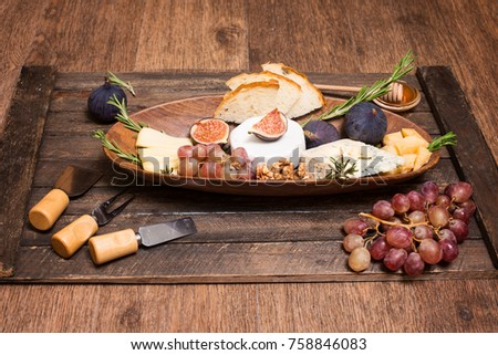 Cheese board. Various types of cheese. Cheese plate with cheeses Parmesan, Brie, Camembert and Roquefort  serving with grapes, honey, nuts, olives, figs  and bread on wooden board.