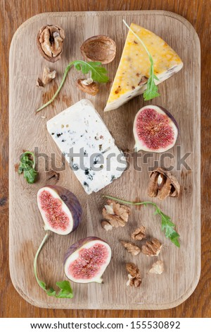Cheese board with blue cheese, nut cheese, fresh figs and nuts