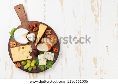Cheese board with grapes and nuts. Wine snaks. Top view with space for your text