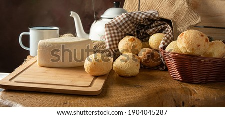 Cheese bread, Brazilian breakfast arrangement, cheese bread, white cheese, kettle and accessories, dark abstract background, selective focus.