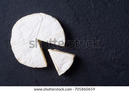 Cheese brie on dark stone background . Top view with space for text