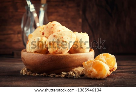 Cheese buns in wooden bowl, rustic kitchen table background, copy space, selective focus