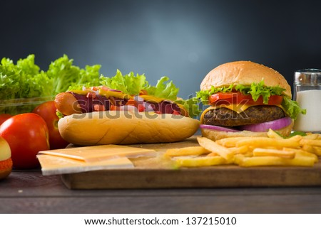 cheese burger and hot dogs with plenty of fast foods ingredients on the background