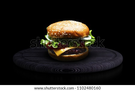 Cheese burger with grilled meat, cheese, tomato, salad and onion rings. Close-up of delicious fresh home made burger on black wooden board on a black background.