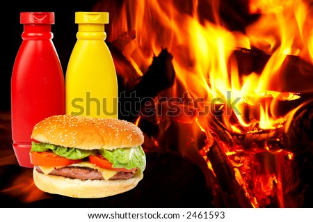 Cheese burger with mustard and ketchup bottles over a flames background