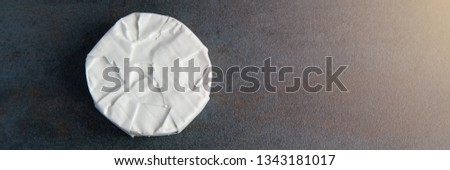 Cheese camembert or brie on dark stone background. Copy space.  Studio photo. Top view.