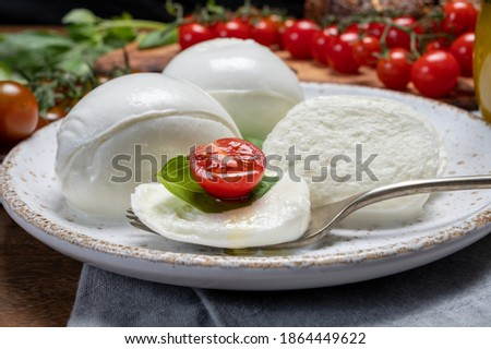 Cheese collection, eating of white soft Italian cheese mozzarella, served with red cherry tomatoes, fresh basil leaves close up Zdjęcia stock ©