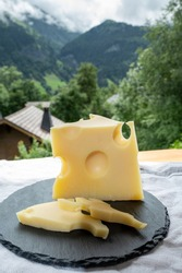 Cheese collection, French cow cheese emmental and french mountains village in Haute-Savoie in summer on background