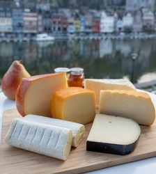 Cheese collection, tasty Belgian abbey cheeses made with brown trappist beer and fine herbs and view on Maas river in Dinant, Wallonia, Belgium